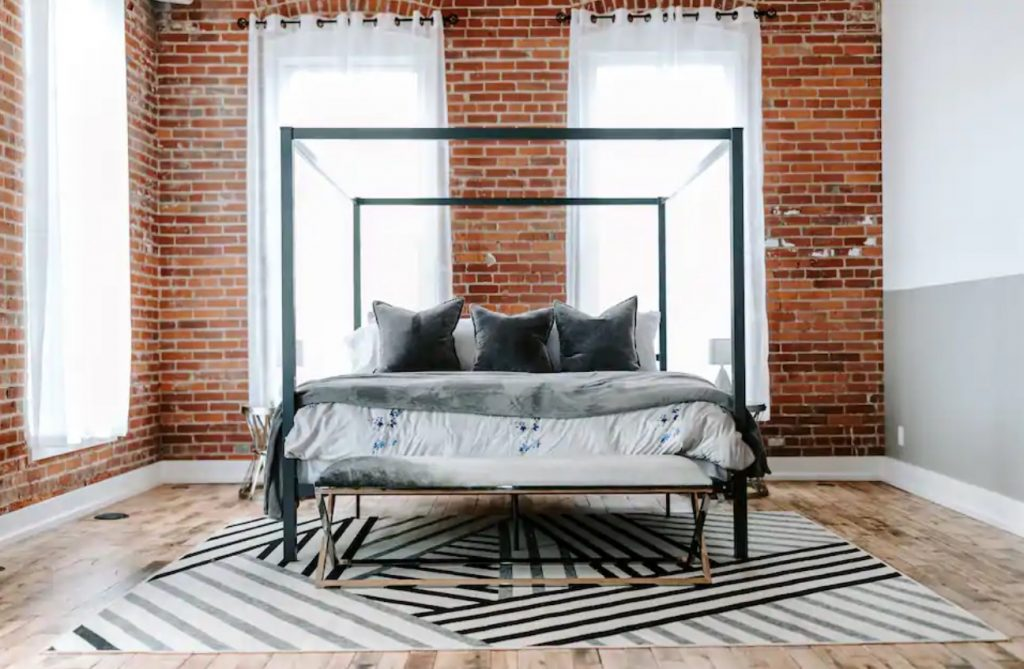A simple but beautifully decorated king size bed in a space with exposed brick walls and floor to ceiling windows