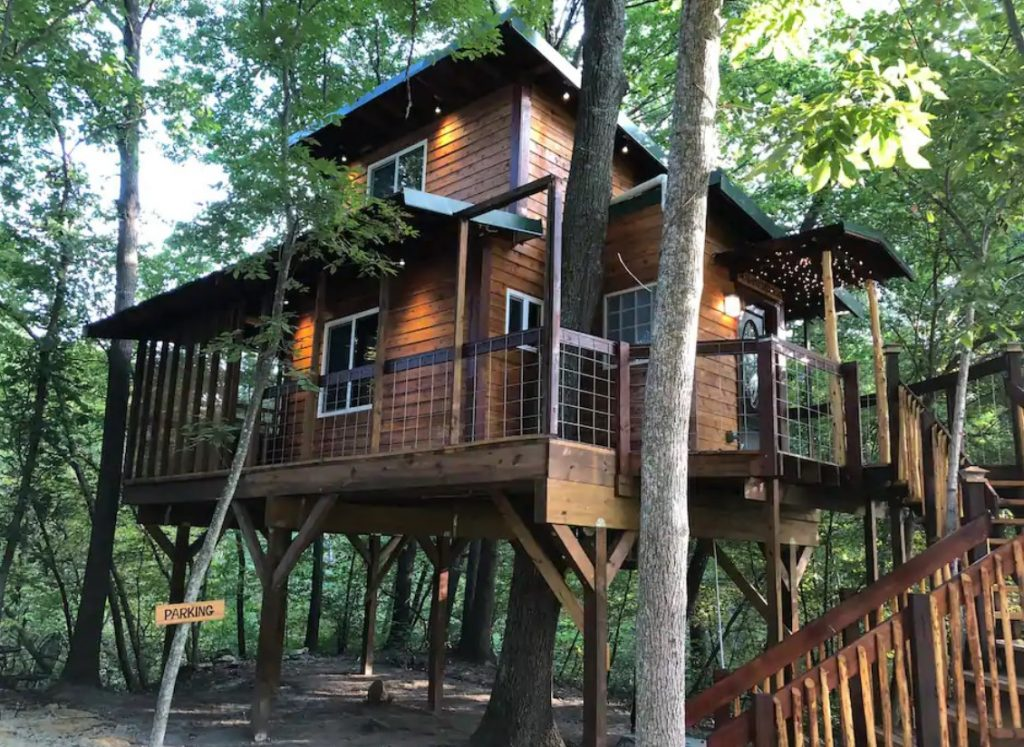 A treehouse perched in the forests of Kansas with natural wood siding, a black roof, and stairs leading up to the treehouse