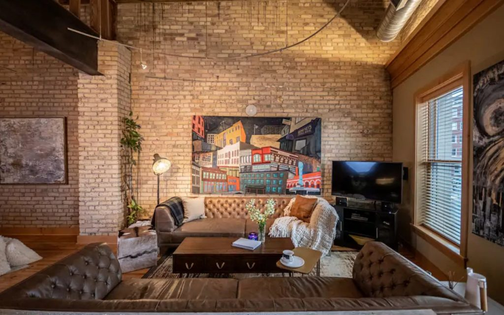 The living room of a large condo in Fargo North Dakota with tall ceilings, exposed brick walls, original art, and leather sofas one of the best Airbnbs in the Midwest
