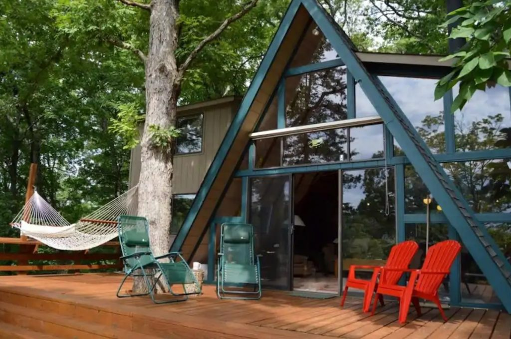 The front of a large A-frame cottage that is painted a dark teal blue and has a massive front deck with chairs and a hammock, surrounded by trees