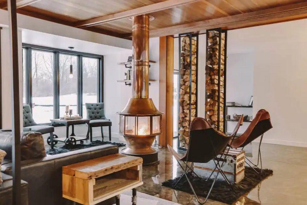 The inside of a modern home's living area with leather couches and chairs and a large copper wood burning fireplace one of the best Airbnbs in the Midwest