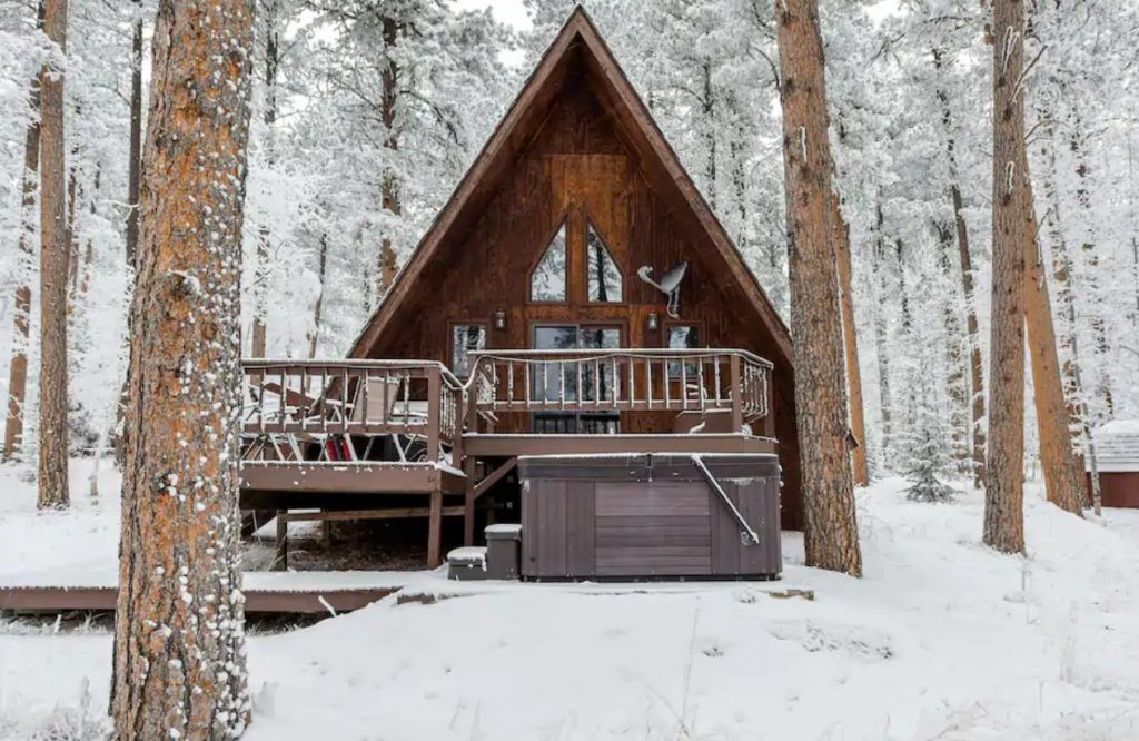 A large natural wood A-frame cabin in the woods in the winter with everything covered in snow one of the best Airbnbs in the Midwest