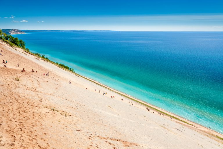 Large sandy dune leading into blue-green waters. Midwest national park.