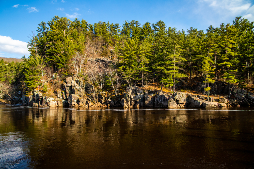 Wisconsin wilderness of evergreen trees and rocky shoreline. National parks in the Midwest.