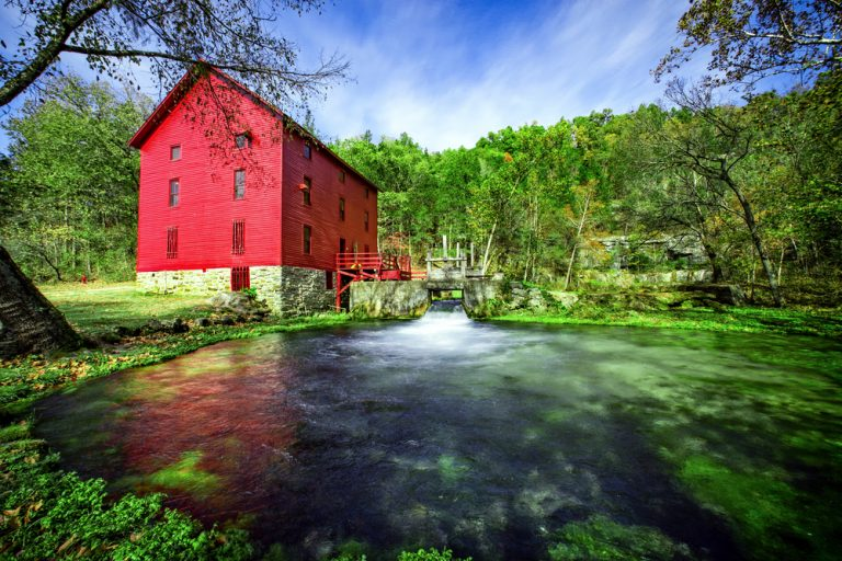 Red barn with waterwheel at national parks in the Midwest.