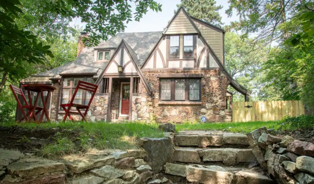 A cottage that looks like it is straight out of a storybook with stone siding and surrounded by trees in Omaha Nebraska