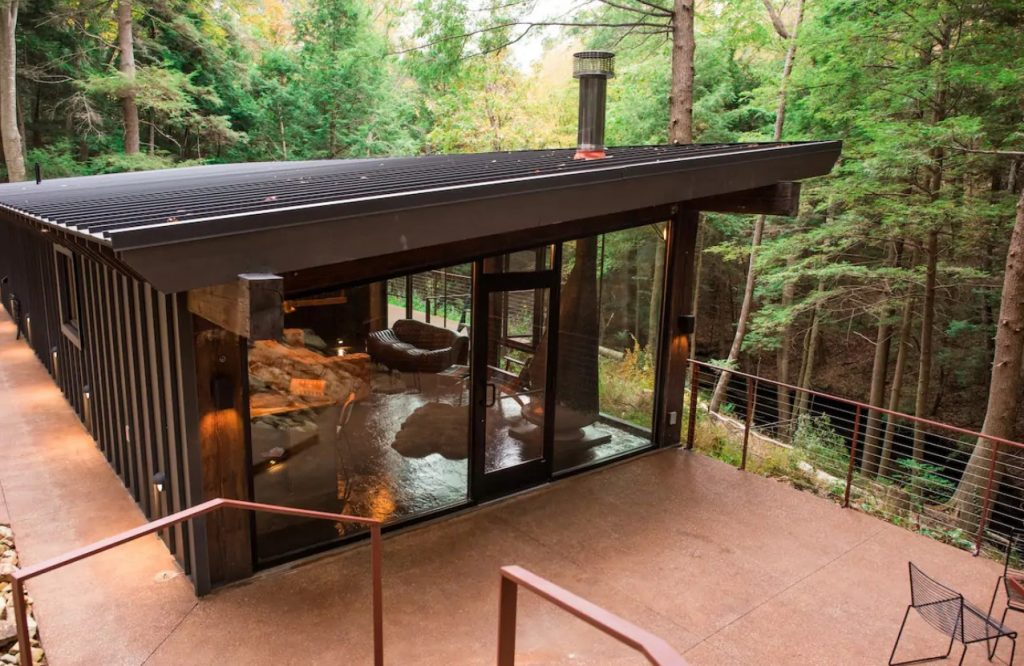 The outside of a modern cabin that has many glass walls and a large patio that overlooks Hocking Hills State Park in Ohio