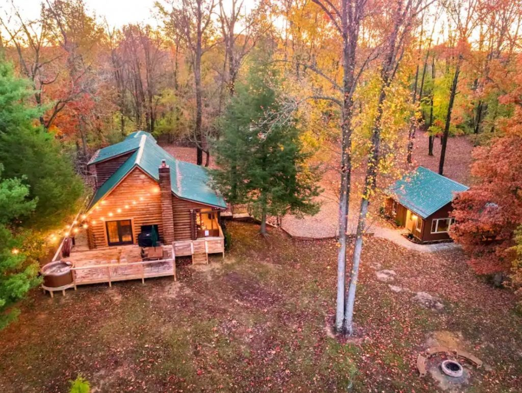 An aerial view of a large log cabin with string lights on a deck and a smaller log cabin in the woods surrounded by trees in the fall one of the best Airbnbs in the midwest