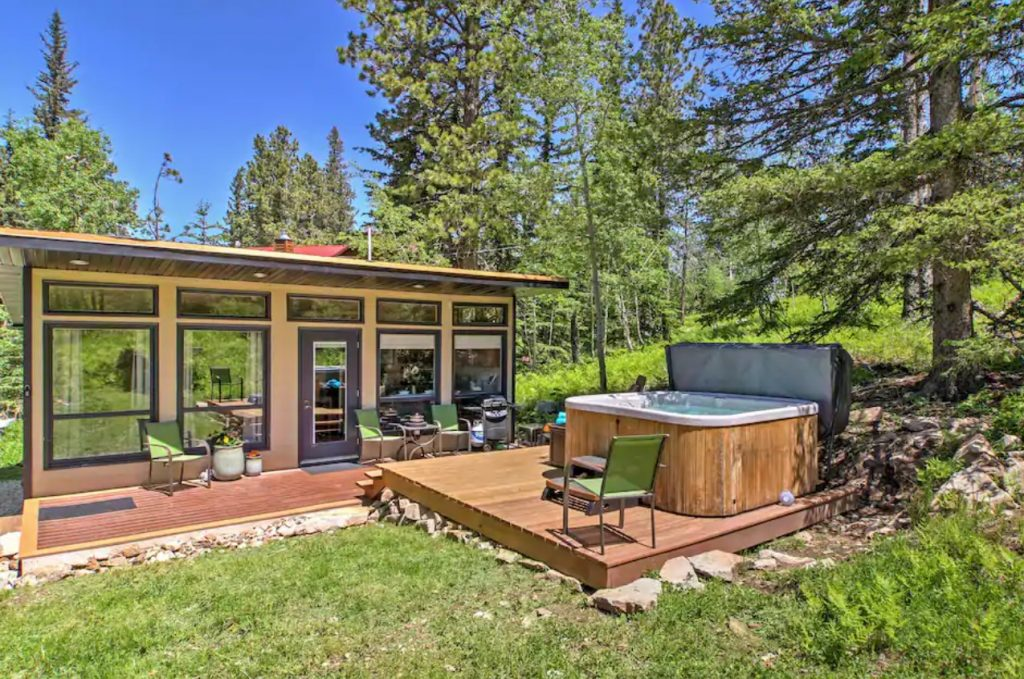 A cabin with plenty of windows surrounded by greenery with a hot tub in front of it in the Black Hills of South Dakota