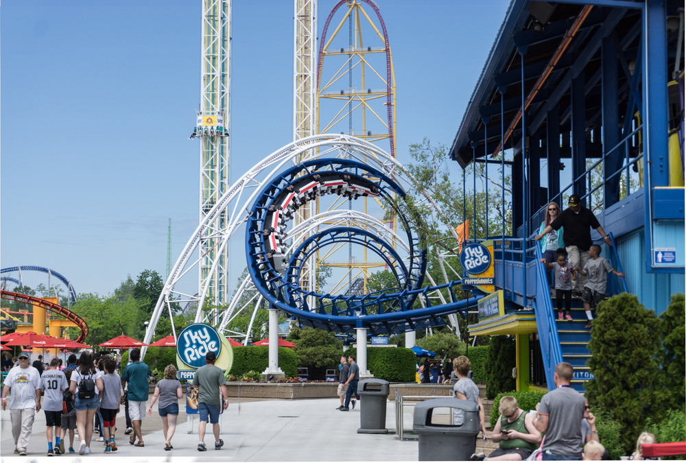 Cedar Point blue roller coaster in foreground with thrill rides in background.
