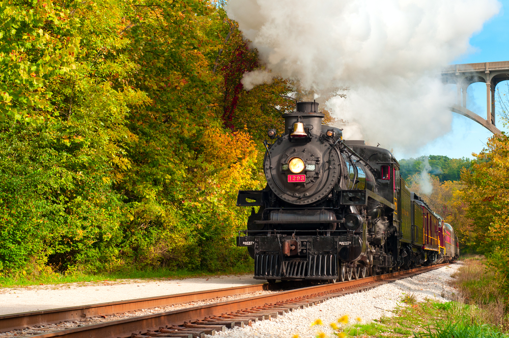 Black engine of passenger train in Cuyahoga Valley National Park with green trees on either side of the tracks.