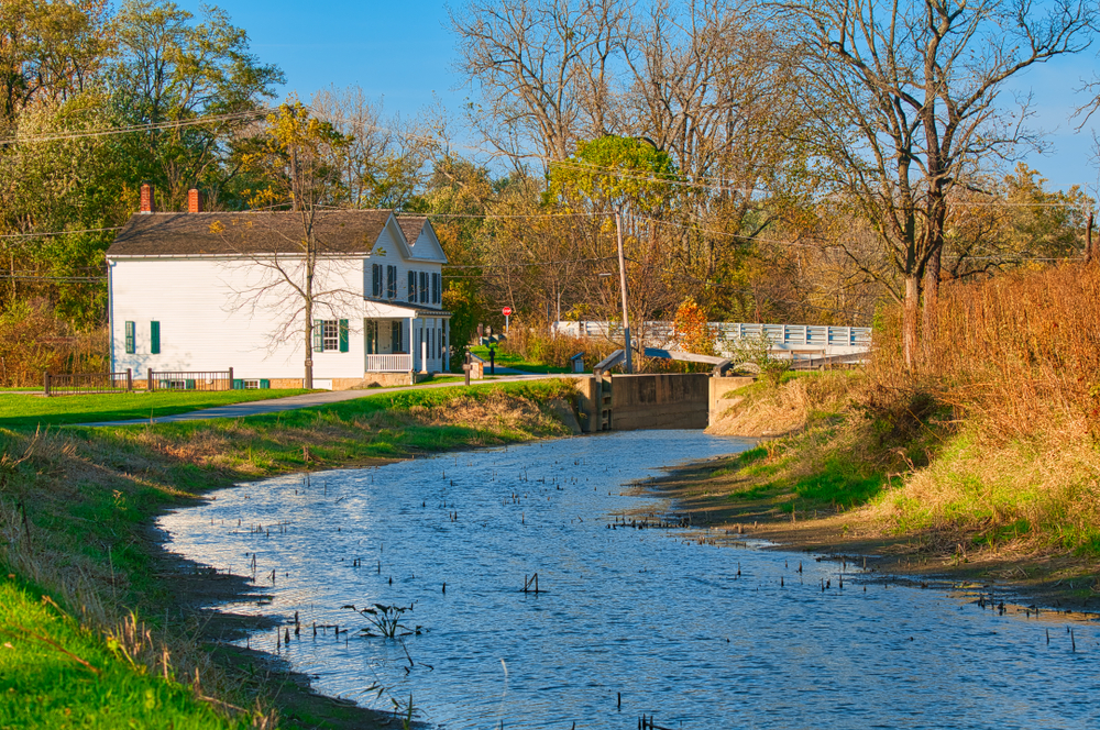 White homes in front of walking trail with river in foreground and autumn trees