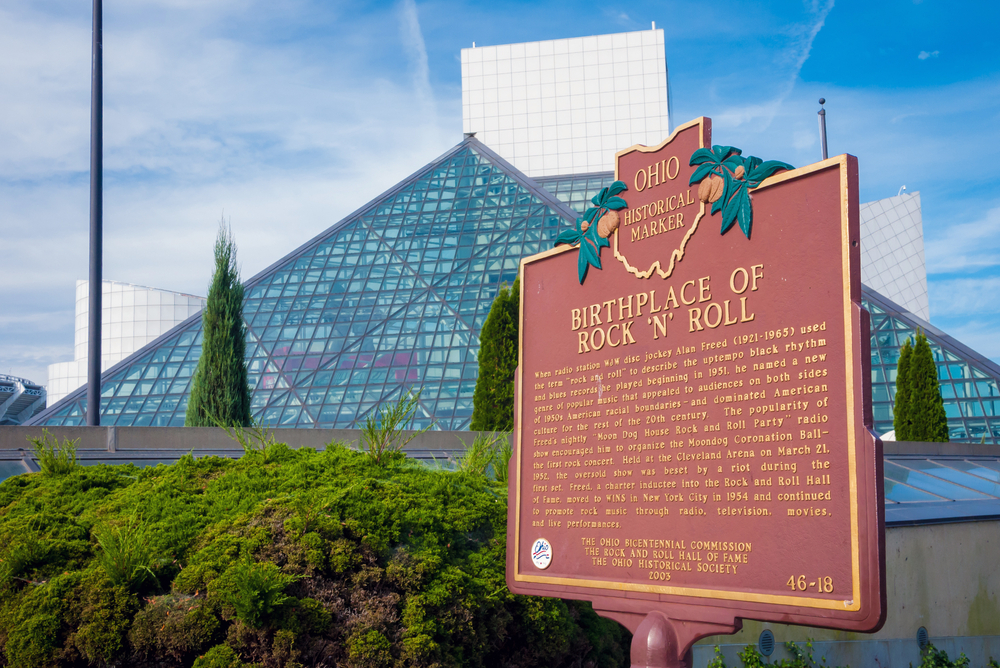 Brown Ohio historical marker explaining the Rock & Roll Hall of Fame with the glass pyramids in the background.