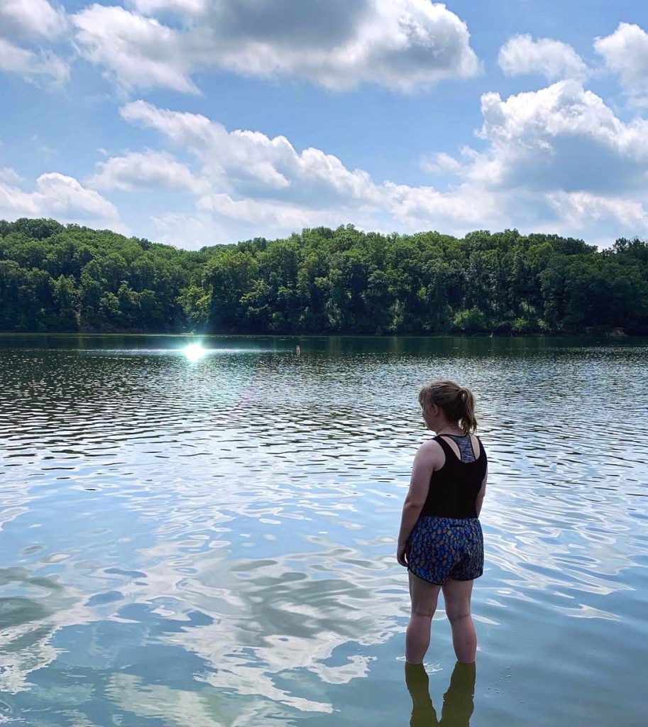 Girl stands looking out over sunny lake lined with lush, green trees at park.