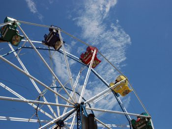 Part of a Ferris Wheel against a blue sky at Bay Beach amusement park in the Midwest