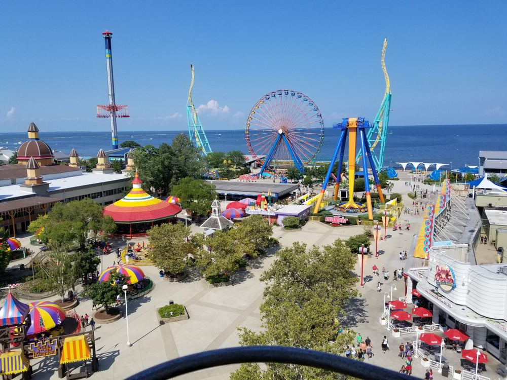 A high view of an amusements park in the midwest with a ferris wheel and the ocean in the background