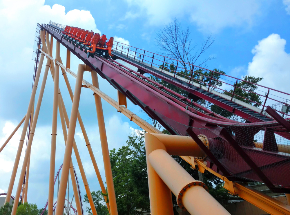 A blue and yellow roller coaster viewed from behind as it goes up a steep inlcine