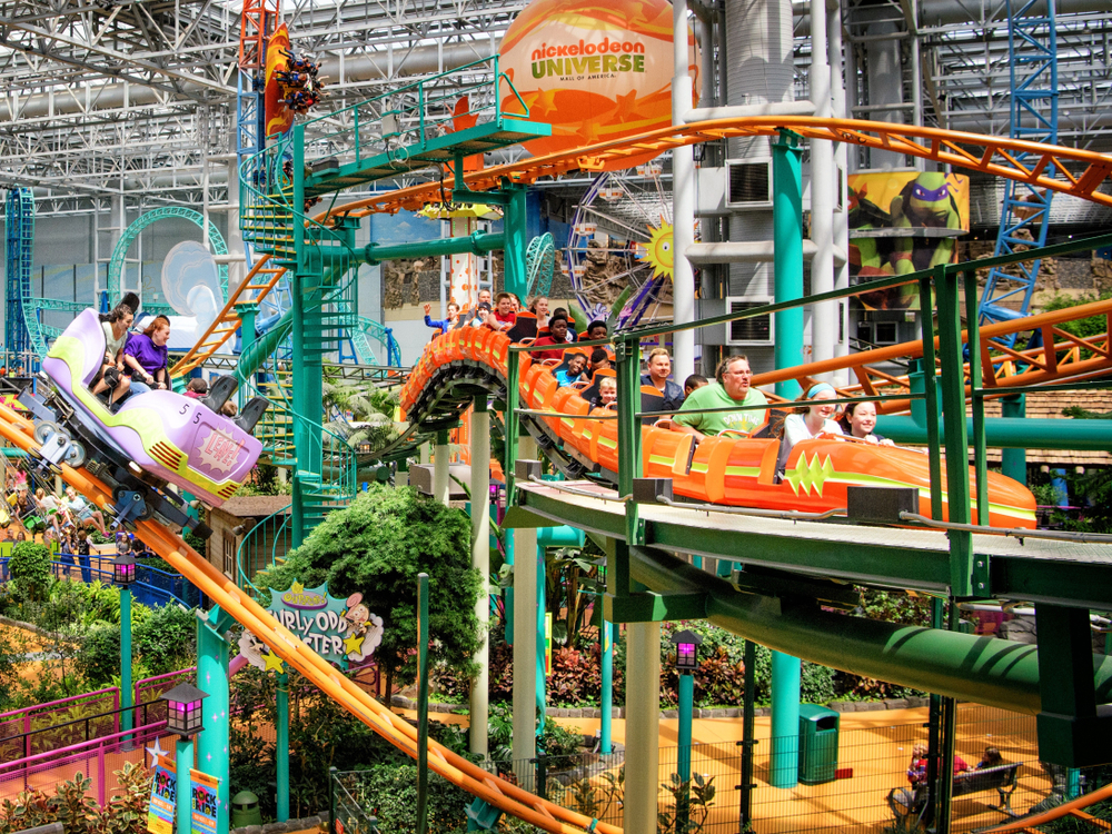 A blue and orange roller coaster with people riding in an amusement park in the Midwest