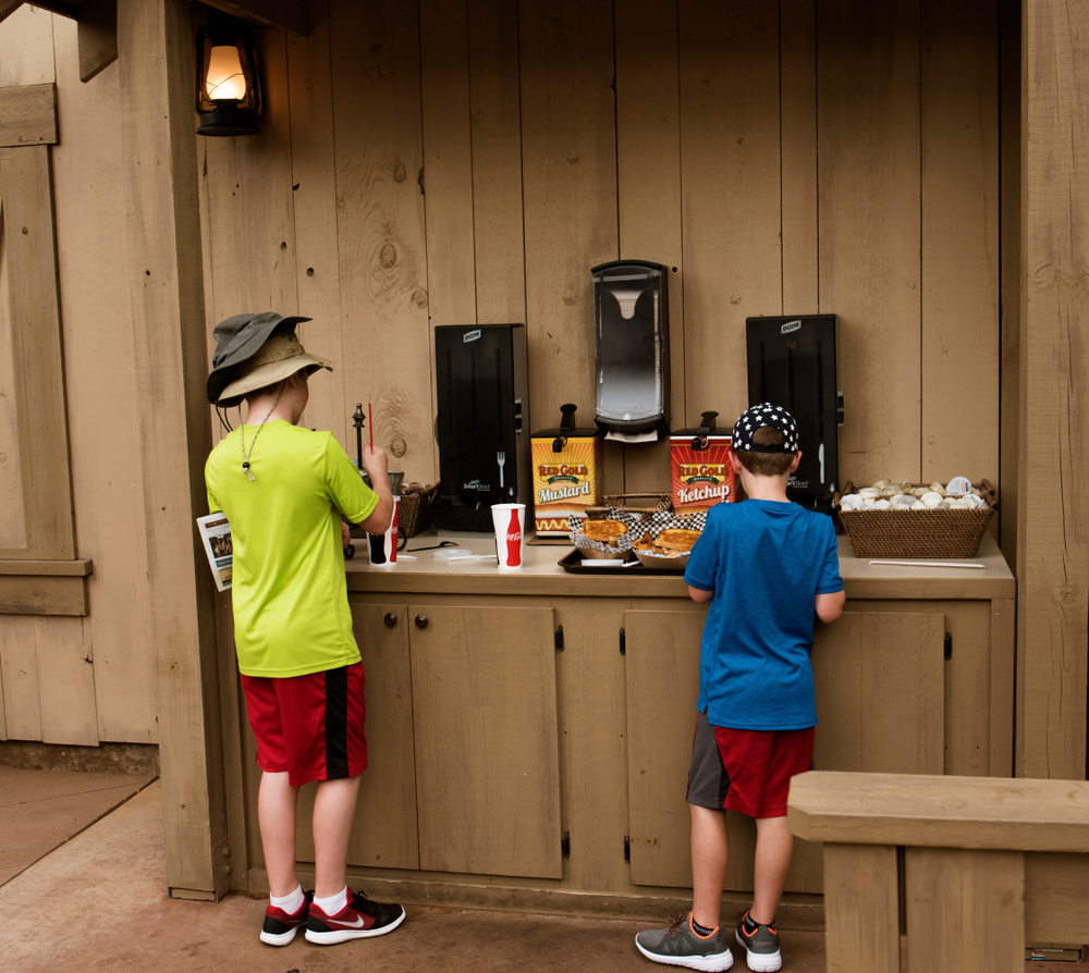 Two children at a fast food stand getting condiments for their meal at Silver Doller City one of the amusements parks in the Midwest