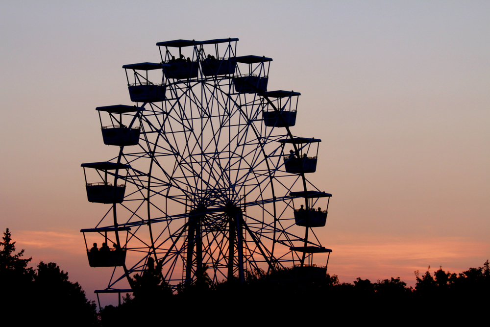 A Ferris wheel against a sunset sky with trees below in an article about amusement parks in the Midwest