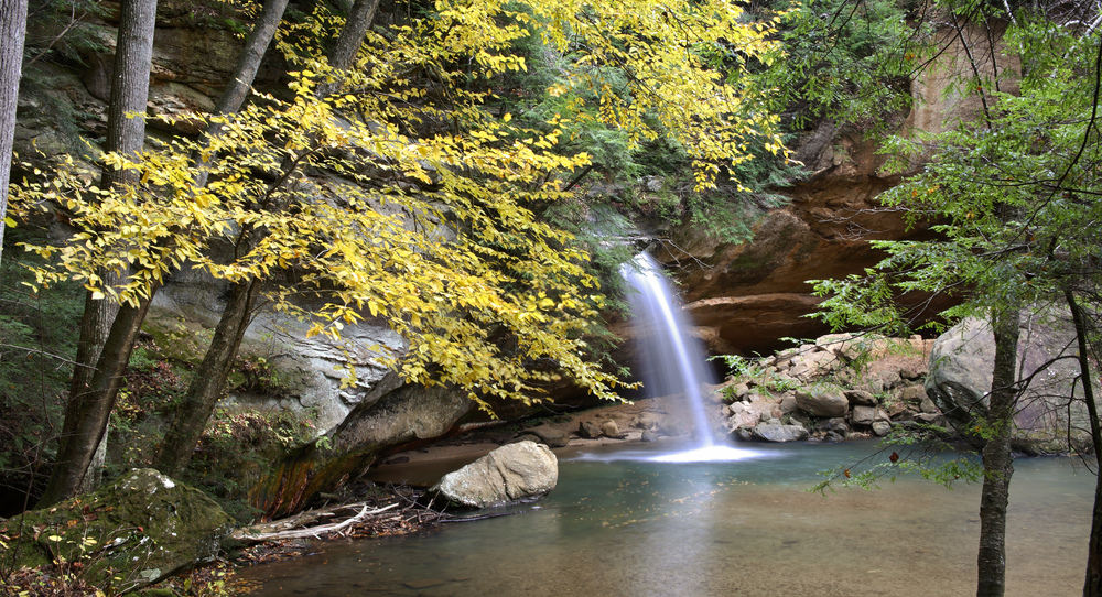 Ohio waterfall in autumn with trees with yellow leaves in foreground.
