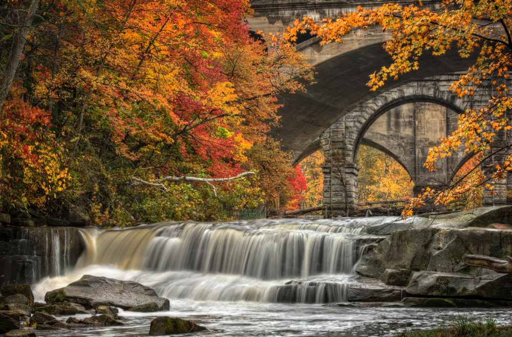 Waterfalls over rocks into stream below with stone bridge and brilliant fall colors on trees in background.