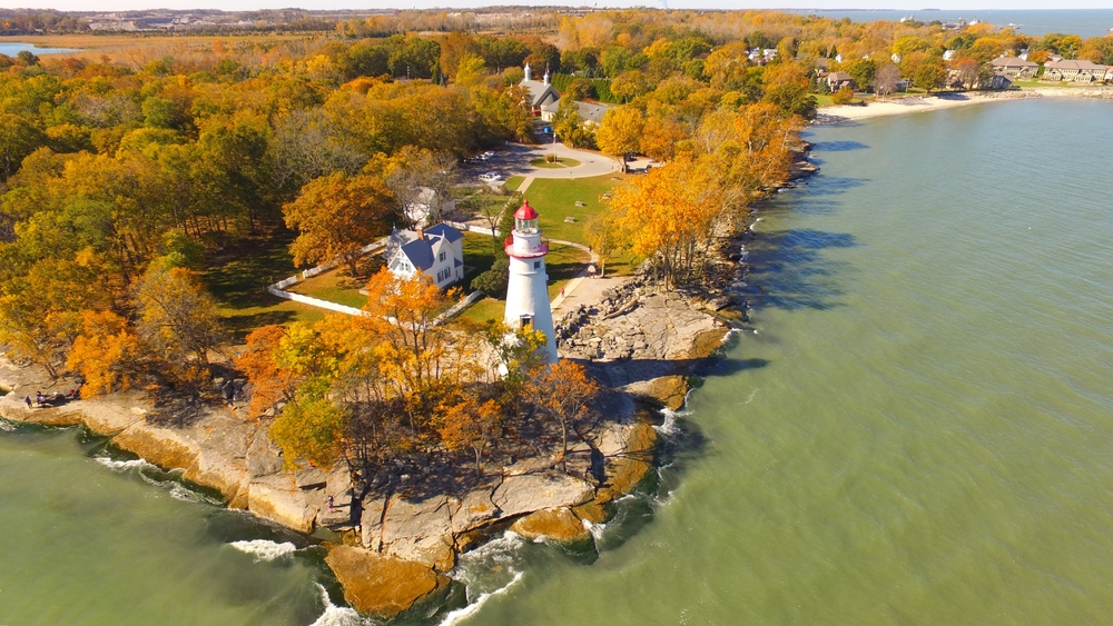 Aerial photo of white lighthouse with fall foliage in Ohio surrounding it with Lake Erie waters  in foreground.