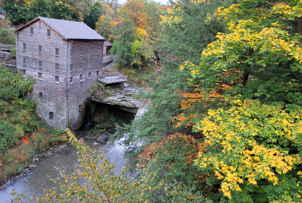 Brick building with deck next to rushing river surrounded by autumnal trees.