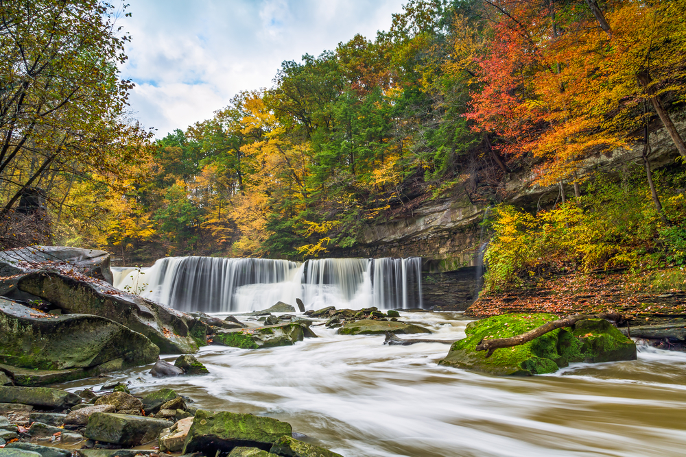 Bright red, orange, and yellow  leaves surround waterfall in Ohio.