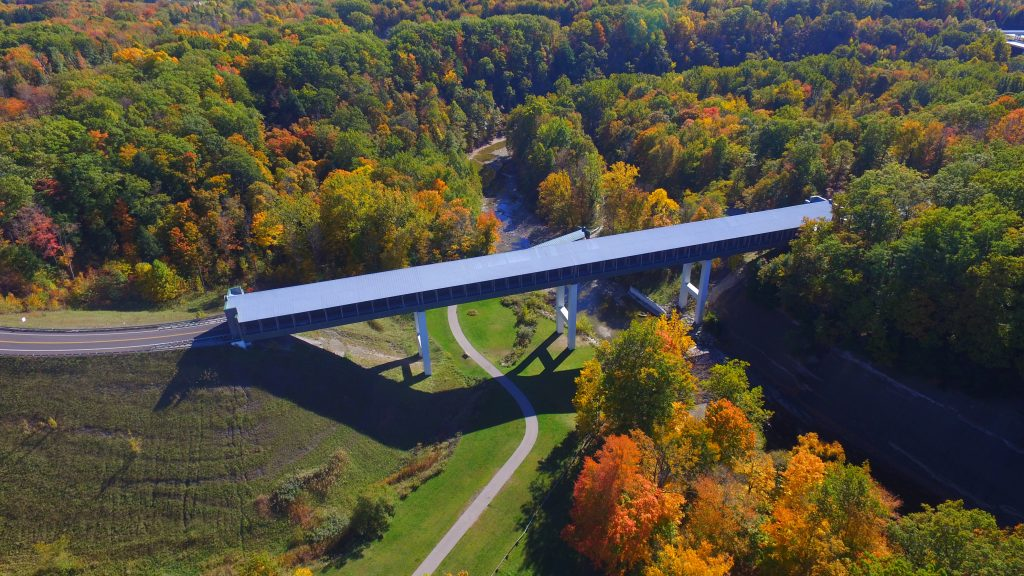 Drone shot of covered bridge with beautiful autumn trees in surrounding countryside.