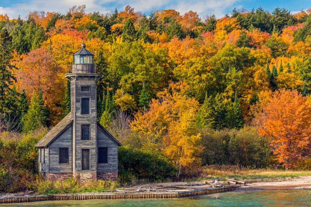 An abandoned wooden Michigan lighthouse on the shores of Lake Superior with autumnal forest in background.