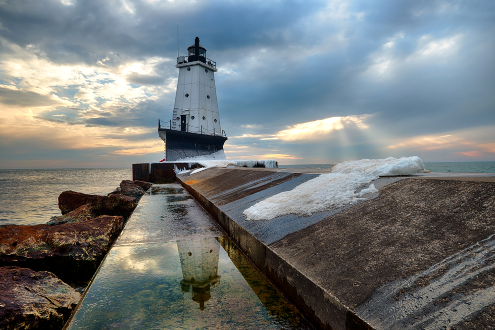 A tall white metal Michigan lighthouse on the end of a long pier with  large rocks to left and sunset in background.