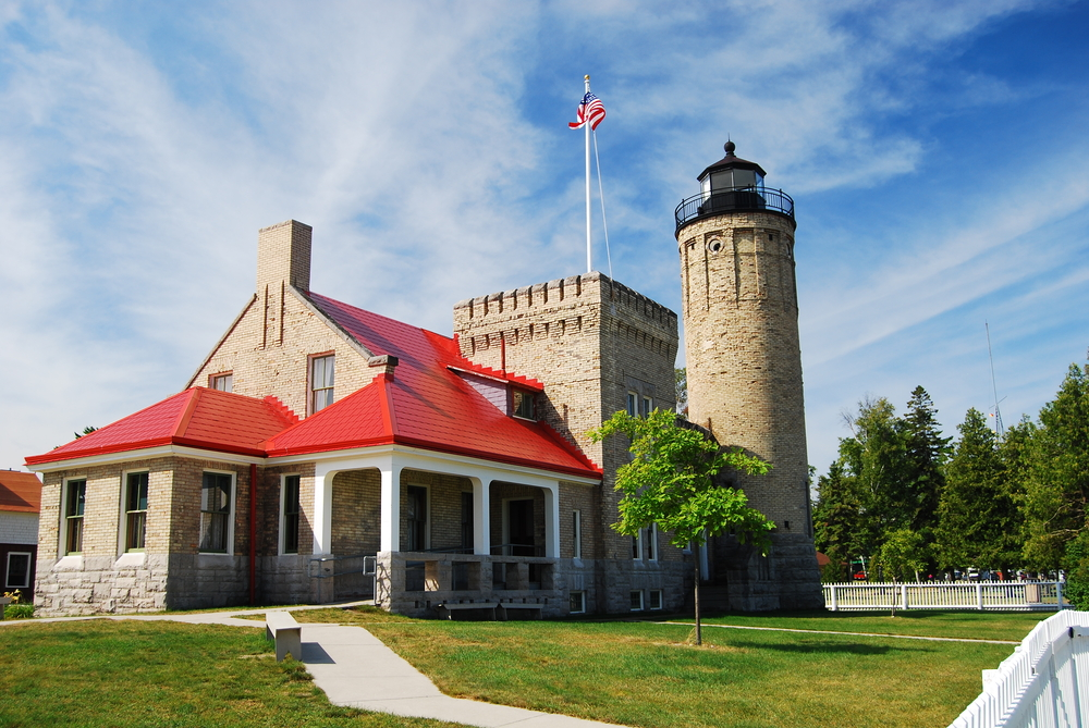A large brown stone lighthouse that resembles a castle with a square turret and a red roof lighthouses in Michigan