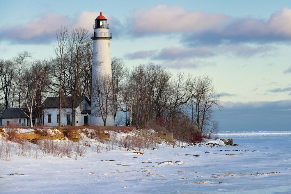 A tall white lighthouse in Michigan on the edge of lake in winter with snow all around.