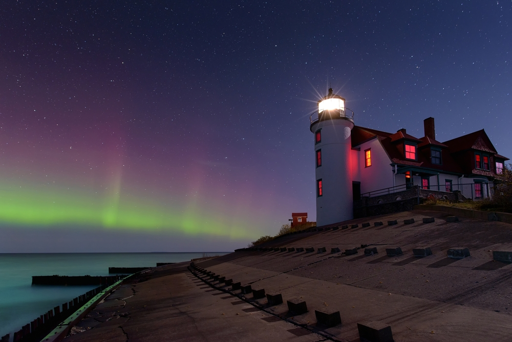 White lighthouse in Michigan with red roof, illuminated from within. Northern Lights in sky background.