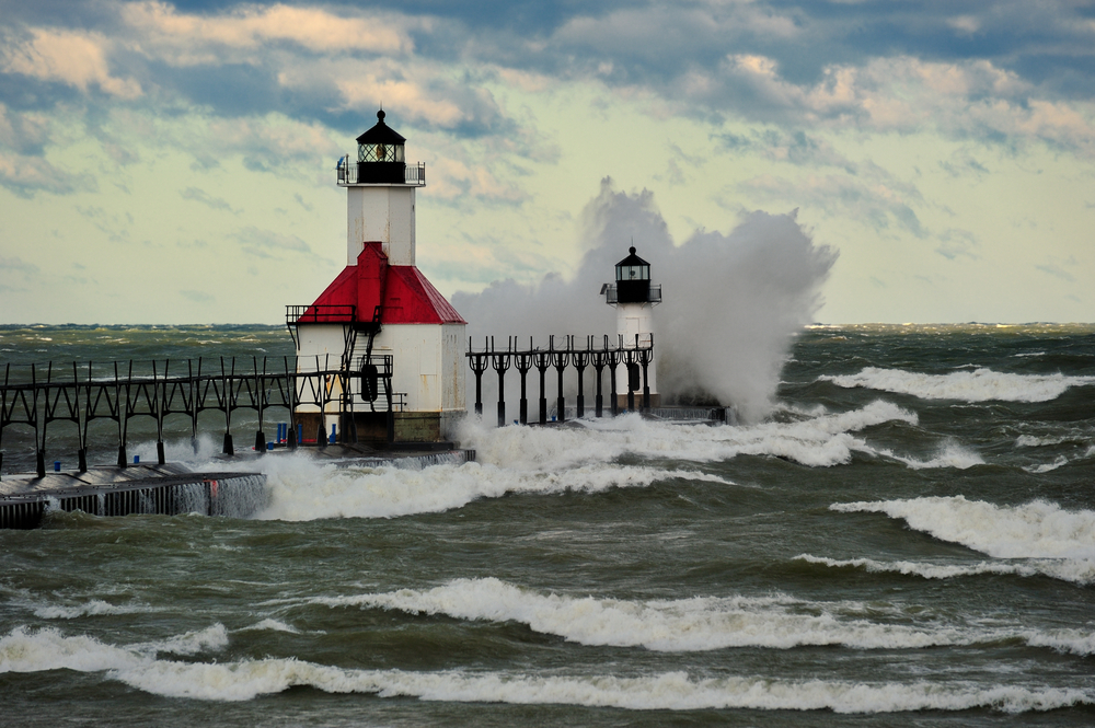 Two Michigan lighthouses at end of pier with large wave crashing into them.