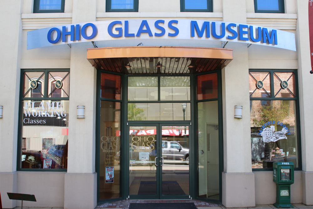 Large glass doors and windows of glass museum with blue letters: Ohio Glass Museum, One of the best things to do in Hocking Hills.