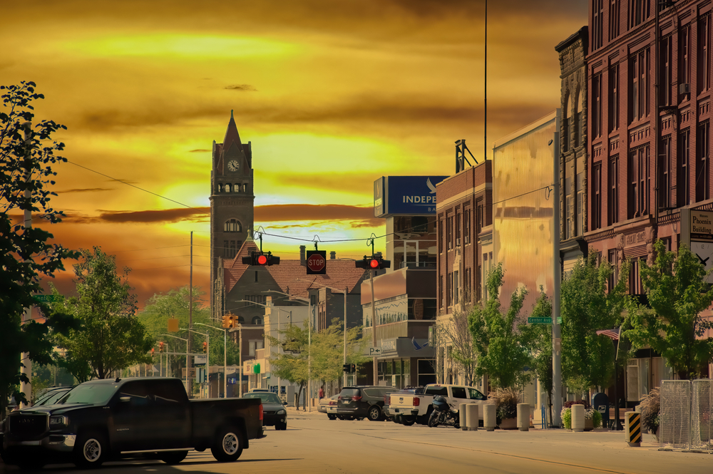 A charming street in Bay City Michigan as the sun is going down with a dark yellow sky