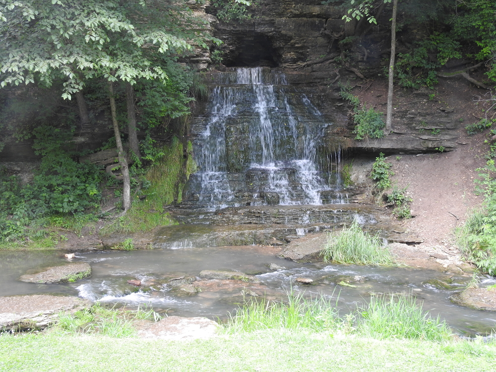 A waterfall tumbling over the rockface. Spook Cave is in the background one of the caves in Iowa
