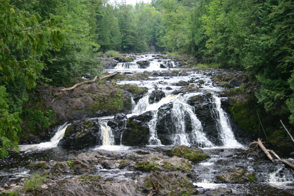 Copper Falls in Wisconsin on a summer day surrounded by lush greenery with a bit of fog