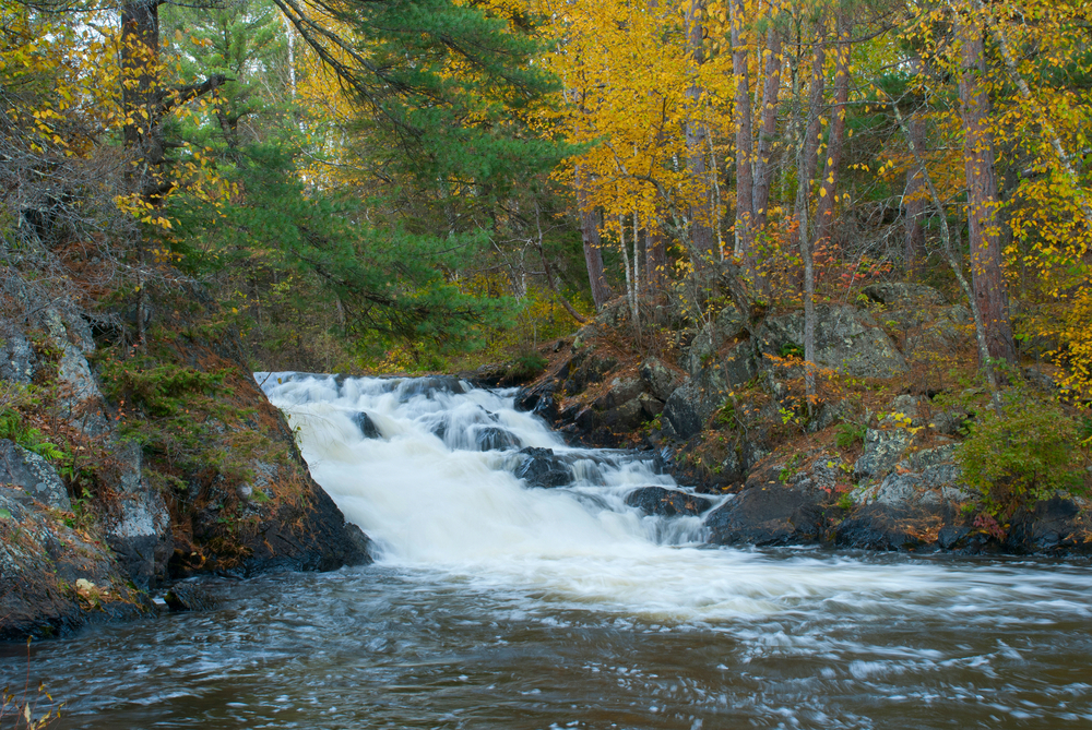 The Eighteen Foot Falls on a cloudy fall day surrounded by trees with leaves changing colors and falling to the ground