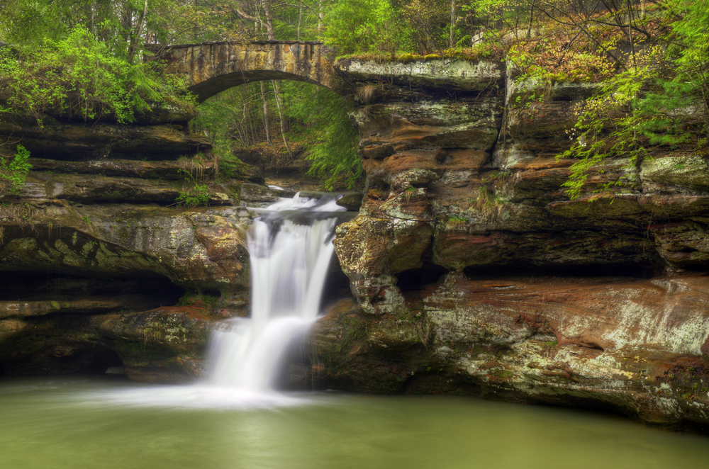 A waterfall down a rock face with a bridge over the top. This is Old Mans cave a great place for Hiking in Hocking Hills