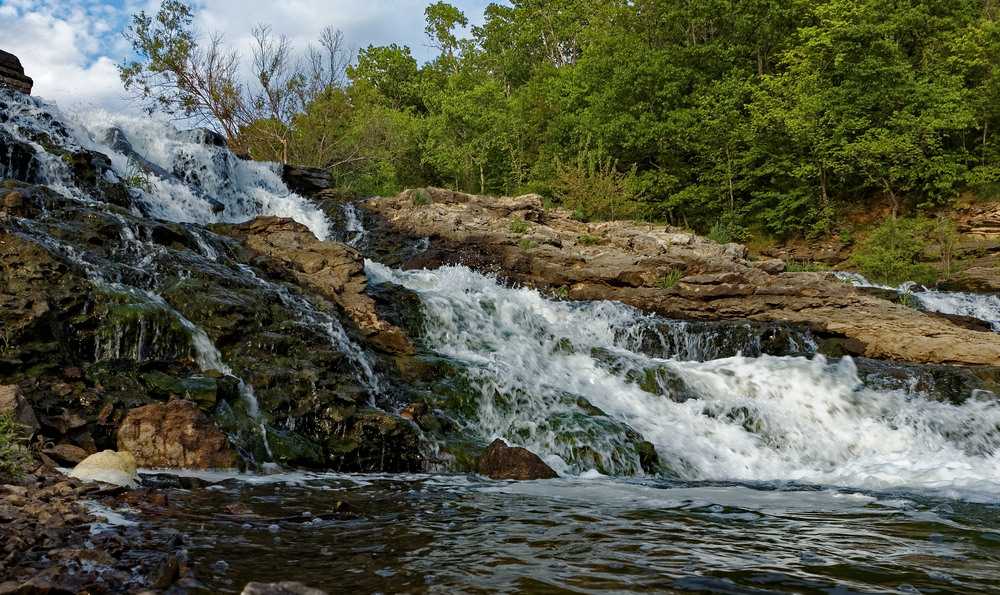 The large waterfall on Lake MacBride in Iowa on a sunny summer day