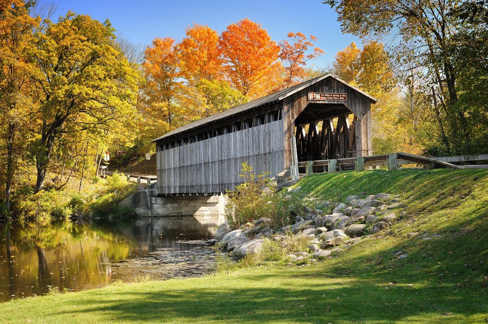 The wooden Fallasburg Covered Bridge in the fall on a sunny day in Michigan during Midwest road trips.