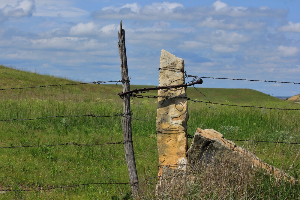 A limestone rock being used as a makeshift fence post on the Post Rock Scenic Byway one of the best Midwest Road Trips