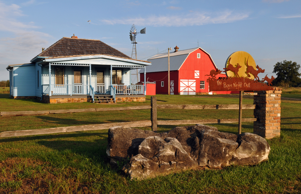 Two buildings restored including a blue farm home and a classic red barn with a windmill in the replica town of Red Oak II in Missouri on a sunny day