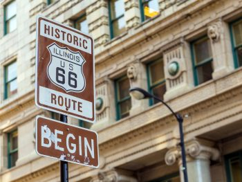 a sign in chicago marking the beginning of historic route 66 one of the best midwest road trips