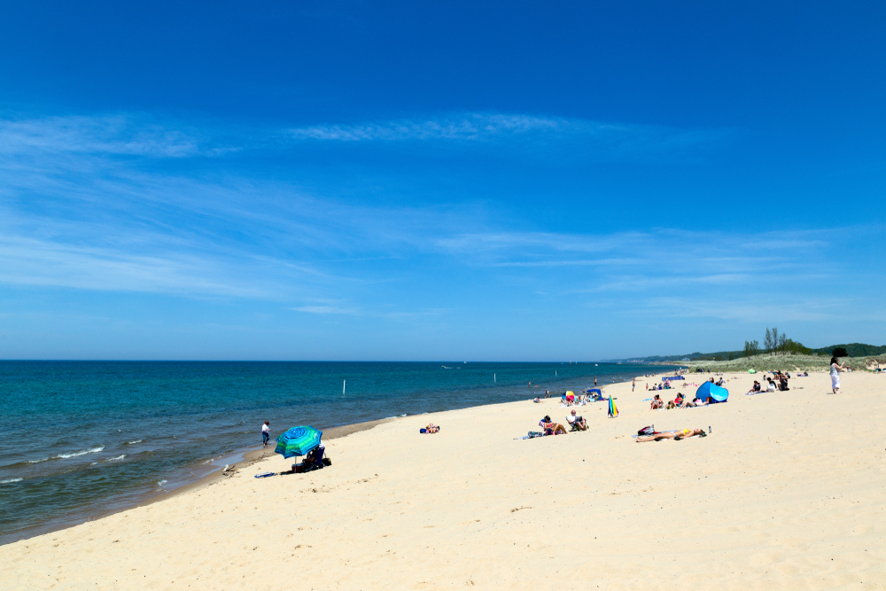 A beautiful white sandy beach on a bright sunny day with clear blue skies in Saugatuck Michigan