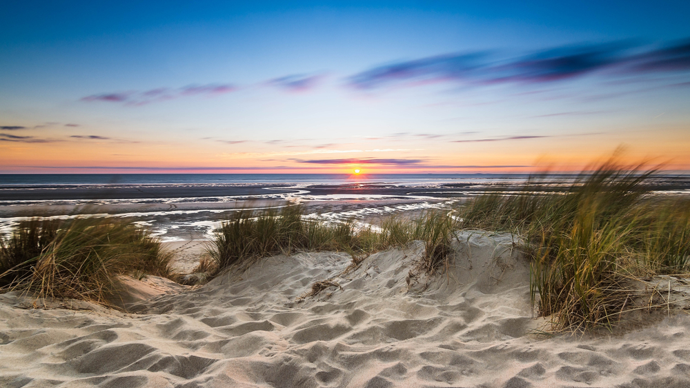 Sandy dunes at Sleeping Bear Dunes National Lakeshore one of the best national parks in Michigan at twilight looking out onto the lake