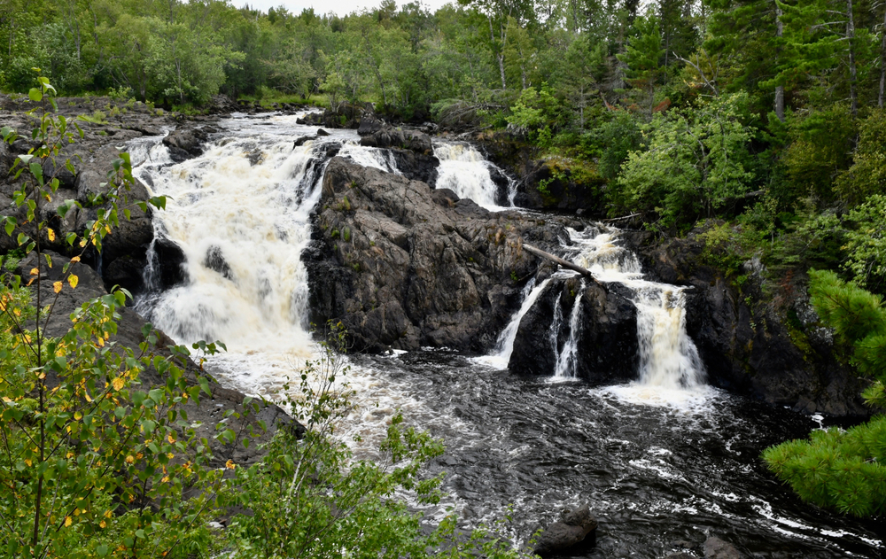 A large waterfall in one of the small towns in Minnesota surrounded by greenery